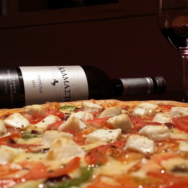 Mouth watering aka uber yummy. Greek-style pizza with feta cheese, olives, fresh tomato and bell peppers.  For this ideal friday night comfort food, a glass of a very rare 100% Mavroudi varietal wine is *perfect* !  #foodie #pizza #greekstyle #yum #drinkgreek #greekdinner #yummy #inmyglass #rare #redwine #wine #vino #mavroudi #adamasto #untamed #greekgrapes #greekwine #grapes #indigenousgrapes #greece #fridaynight #home #comfort